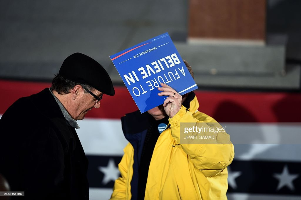 A supporter of US Democratic presidential candidate Bernie Sanders holds a campaign poster as he arrives for a primary night rally in Concord, New Hampshire, on February 9, 2016. / AFP / Jewel Samad