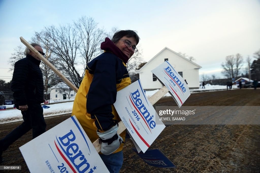 A supporter of US Republican presidential candidate Bernie Sanders arrives with campaign posters outside the town hall as local residents vote for the first US presidential primary in Canterbury, New Hampshire, on February 9, 2016. New Hampshire began voting on February 9 in the first US presidential primary with Republican Donald Trump calling on supporters to propel him to victory and Democrat Bernie Sanders primed to upstage Hillary Clinton. The northeastern state, home to just 1.3 million people, sets the tone for the primaries and could shake out a crowded Republican field of candidates pitting Trump and arch-conservative Senator Ted Cruz against more establishment candidates led by Senator Marco Rubio. / AFP / Jewel Samad