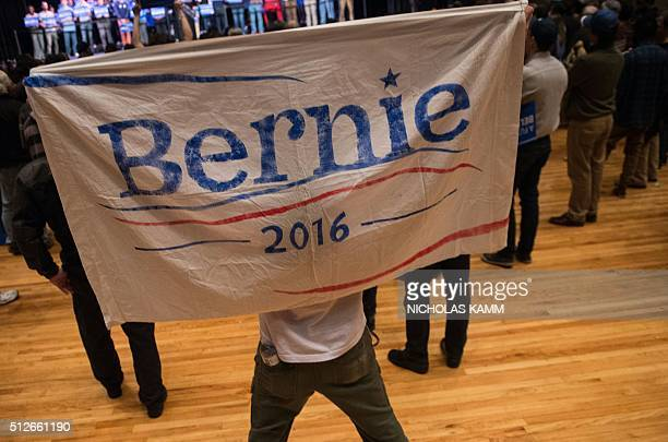 A supporter of US Democratic presidential candidate Bernie Sanders holds up a sign as Sanders addresses rally at the Township Auditorium in Columbia...