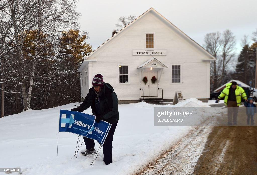 A supporter of US Republican presidential candidate Hillary Clinton adjusts a campaign poster outside the town hall as local residents vote for the first US presidential primary in Canterbury, New Hampshire, on February 9, 2016. New Hampshire began voting on February 9 in the first US presidential primary with Republican Donald Trump calling on supporters to propel him to victory and Democrat Bernie Sanders primed to upstage Hillary Clinton. The northeastern state, home to just 1.3 million people, sets the tone for the primaries and could shake out a crowded Republican field of candidates pitting Trump and arch-conservative Senator Ted Cruz against more establishment candidates led by Senator Marco Rubio. / AFP / Jewel Samad