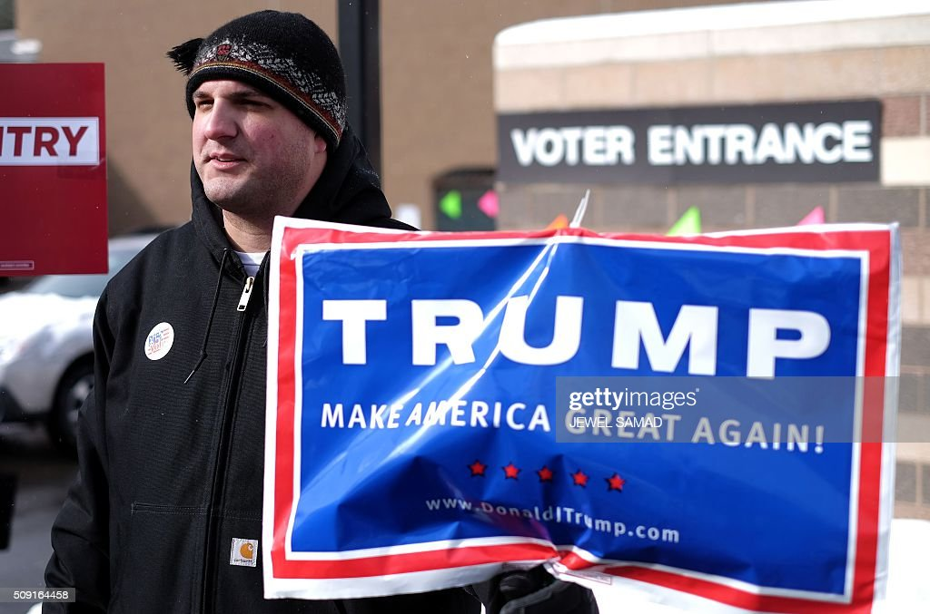 A supporter of US Republican presidential candidate Donald Trump displays a campaign poster as residents vote for the first US presidential primary at a school gym in Concord, New Hampshire, on February 9, 2016. New Hampshire voters headed to polls at the snowy break of day on February 9 for the crucial first US presidential primary, with Donald Trump chasing victory and Hillary Clinton looking to narrow the gap on Bernie Sanders. The northeastern state, home to just 1.3 million people, sets the tone for the primaries -- and could shake out a crowded Republican field as the arch-conservative Senator Ted Cruz and establishment candidates led by Marco Rubio battle for second place behind the frontrunner Trump. / AFP / Jewel Samad