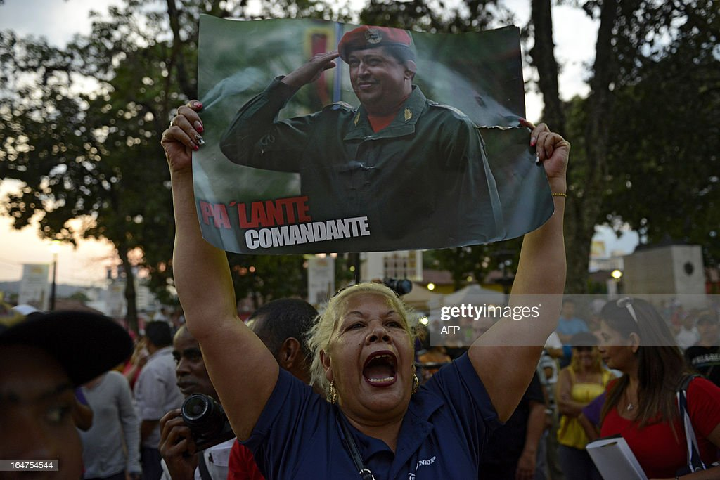 A supporter of Venezuelan former President Hugo Chavez holds a poster with his portrait as she shouts slogans outside a church where opposition presidential candidate Henrique Capriles Radonski is attending a Holy Week mass in Caracas on March, 27, 2013. AFP PHOTO/Leo RAMIREZ