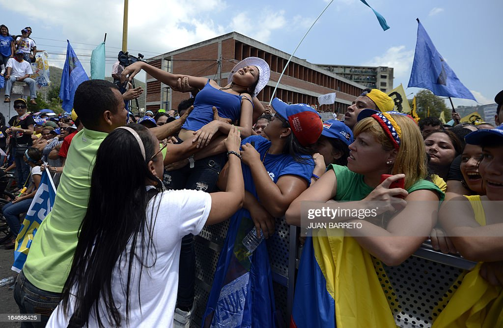 A supporter of Venezuelan opposition presidential candidate Henrique Capriles (not depicted) faints abnd is helped during a rally in Valera, Trujillo state, Venezuela on March 26, 2013. Venezuela will elect its new president on April 14, 2013. AFP PHOTO