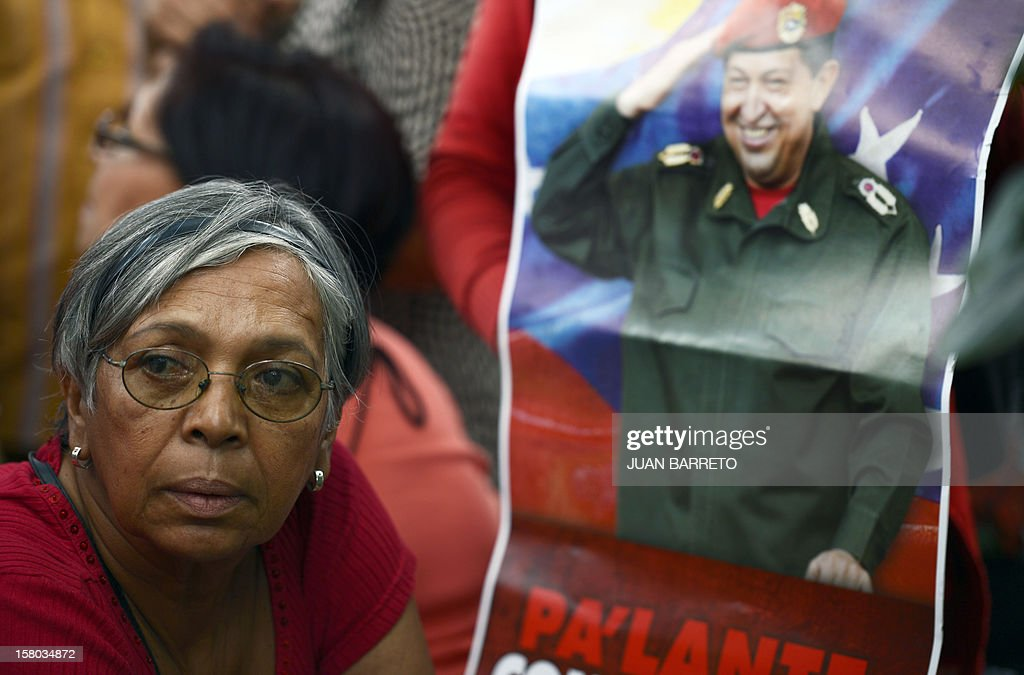 A supporter of Venezuelan President Hugo Chavez attends a rally in Caracas on December 9, 2012. Chavez was poised to head to Cuba Sunday for more cancer surgery, after speaking for the first time of a successor in this oil-rich nation he so thoroughly dominates should he not recover. Treatment is 'absolutely necessary,' the leftist leader said in a bombshell statement on state television in which he admitted he may have to give up the presidency and that Vice President Nicolas Maduro is his chosen successor. AFP PHOTO