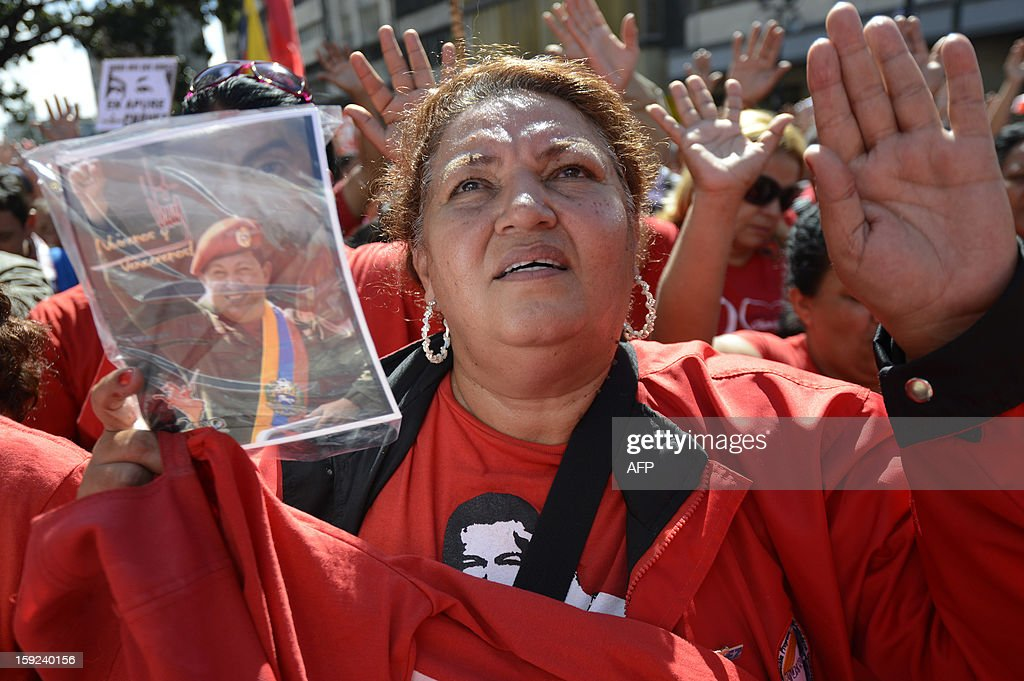 A supporter of Venezuelan President Hugo Chavez gathers outside Miraflores presidential palace during an event in homage of Chavez, in Caracas on January 10, 2013. With Chavez ailing and absent, Venezuela's leftist government launches a new presidential term with a display of popular support on the day he was to be inaugurated. The Supreme Court cleared the cancer-stricken president,kwho is recovering from a fourth round of cancer surgery in Havana, to indefinitely postpone his re-inauguration and said his existing administration could remain in office until he is well enough to take the oath. The government has said that he is recovering from complications from surgery, most recently a severe pulmonary infection that had resulted in a 'respiratory insufficiency.' AFP PHOTO/LEO RAMIREZ