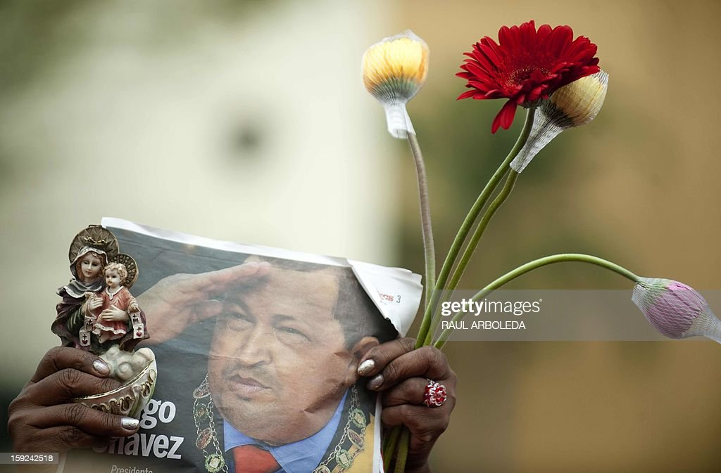 A supporter of Venezuelan President Hugo Chavez gathers with others outside Miraflores presidential palace during an event in homage of Chavez, in Caracas on January 10, 2013. With Chavez ailing and absent, Venezuela's leftist government launches a new presidential term with a display of popular support on the day he was to be inaugurated. The Supreme Court cleared the cancer-stricken president,kwho is recovering from a fourth round of cancer surgery in Havana, to indefinitely postpone his re-inauguration and said his existing administration could remain in office until he is well enough to take the oath. The government has said that he is recovering from complications from surgery, most recently a severe pulmonary infection that had resulted in a 'respiratory insufficiency.' AFP PHOTO/Raul ARBOLEDA