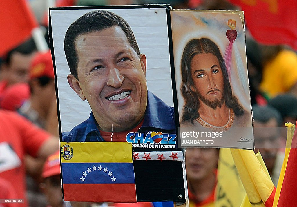 A supporter of Venezuelan President Hugo Chavez holds a poster of Chavez next to an image of Jesus Christ, outside Miraflores presidential palace during an event in homage of nation's leader, in Caracas on January 10, 2013. With Chavez ailing and absent, Venezuela's leftist government launches a new presidential term with a display of popular support on the day he was to be inaugurated. The Supreme Court cleared the cancer-stricken president,kwho is recovering from a fourth round of cancer surgery in Havana, to indefinitely postpone his re-inauguration and said his existing administration could remain in office until he is well enough to take the oath. The government has said that he is recovering from complications from surgery, most recently a severe pulmonary infection that had resulted in a 'respiratory insufficiency.' AFP PHOTO/JUAN BARRETO