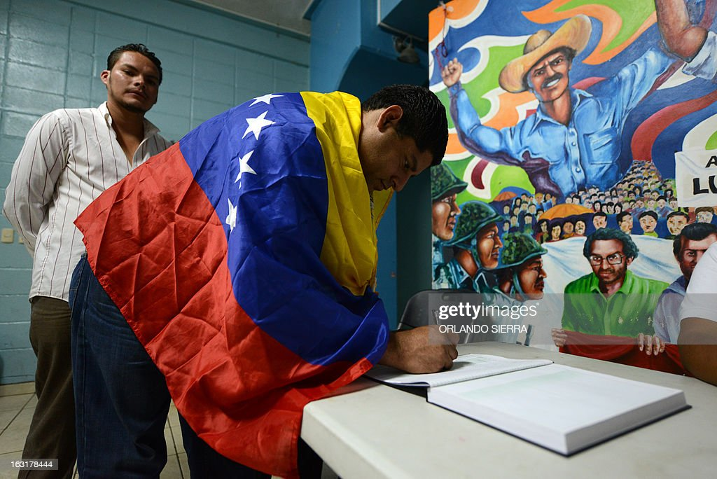 A supporter of Venezuelan President Hugo Chavez signs a condolences book in Tegucigalpa, Honduras on March 5, 2013, after knowing of his death. AFP PHOTO/Orlando SIERRA.