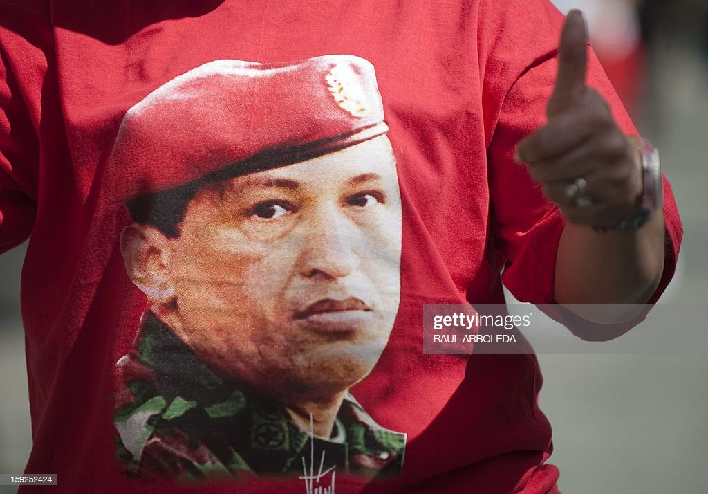 A supporter of Venezuelan President Hugo Chavez wears a t-shirt with his image during an event in homage of Chavez outside Miraflores presidential palace in Caracas on January 10, 2013. With cancer-stricken President Hugo Chavez hospitalized in Cuba, thousands of flag-waving Venezuelans in red shirts filled the streets of Caracas Thursday to inaugurate his new term without him. Bands played anthems from street-side stages as people poured out of buses to make their way on foot toward the Miraflores presidential palace for a symbolic swearing-in of the people in place of Chavez, who is too sick to take the oath of office. AFP PHOTO/Raul ARBOLEDA