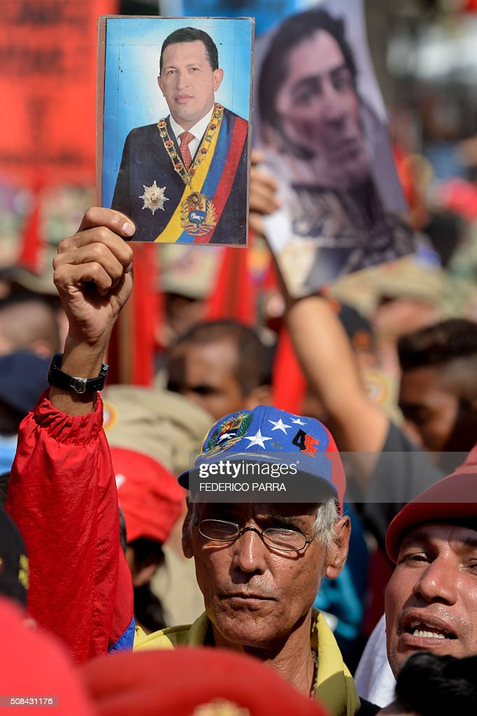 A supporter of Venezuelan President Nicolas Maduro holds a portrait of late Venezuelan President Hugo Chavez during a ceremony to commemorate the...