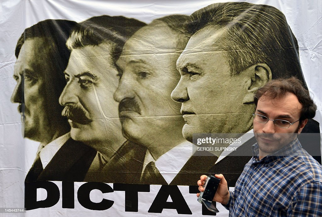 A supporter of Yulia Tymoshenko stands in front of bannerdepicting Adolf Hitler, Stalin, Alexander Lukashenko and Ukrainian President Viktor Yanukovych and marked 'Dictators' during a rally of her supporters in the tent camp in Kiev on May 30, 2012, as they mark 300 days since the leader of the opposition was jailed. Ukraine's general prosecutor said Wednesday the jailed ex-premier Yulia Tymoshenko was cited as a witness in the murder of a deputy, putting fresh pressure on President Viktor Yanukovych's arch-enemy.