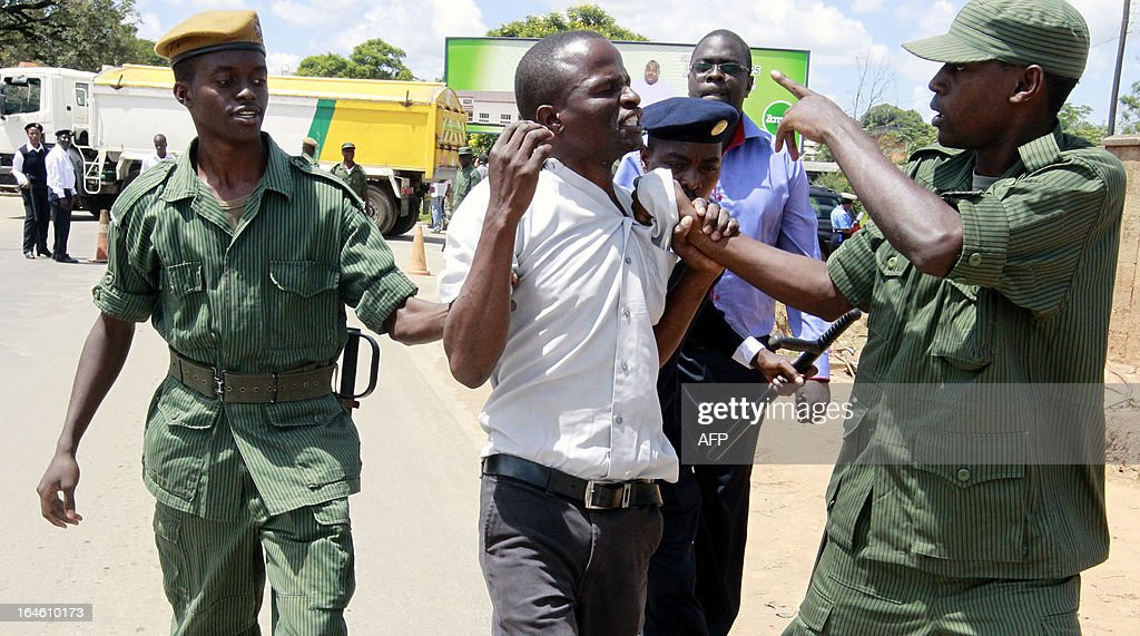 A supporter of Zambia's former President Rupiah Banda is arrested by policemen for misconduct at the Drug Enforcement Commission in Lusaka on March...