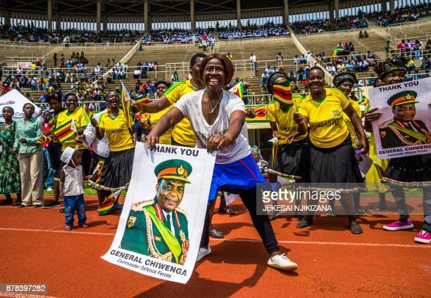 TOPSHOT A supporter of Zimbabwe's new interim President Emmerson Mnangagwa waves a poster of army Chief of Staff General Constantino Chiwenga ahead...