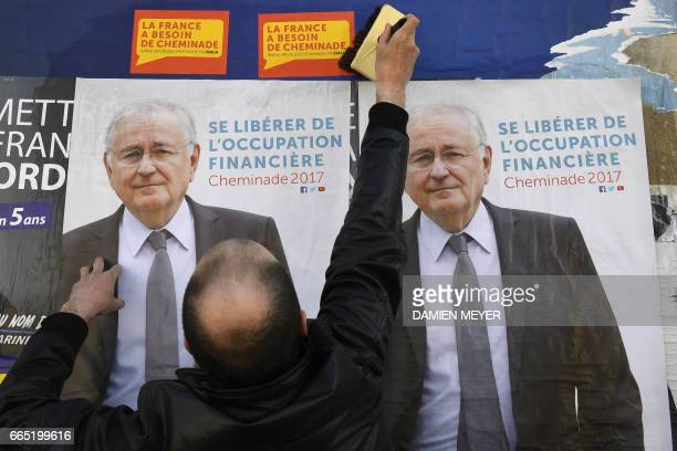 A supporter pastes electoral posters of French presidential election candidate for the Solidarite et Progres party Jacques Cheminade in Retiers...