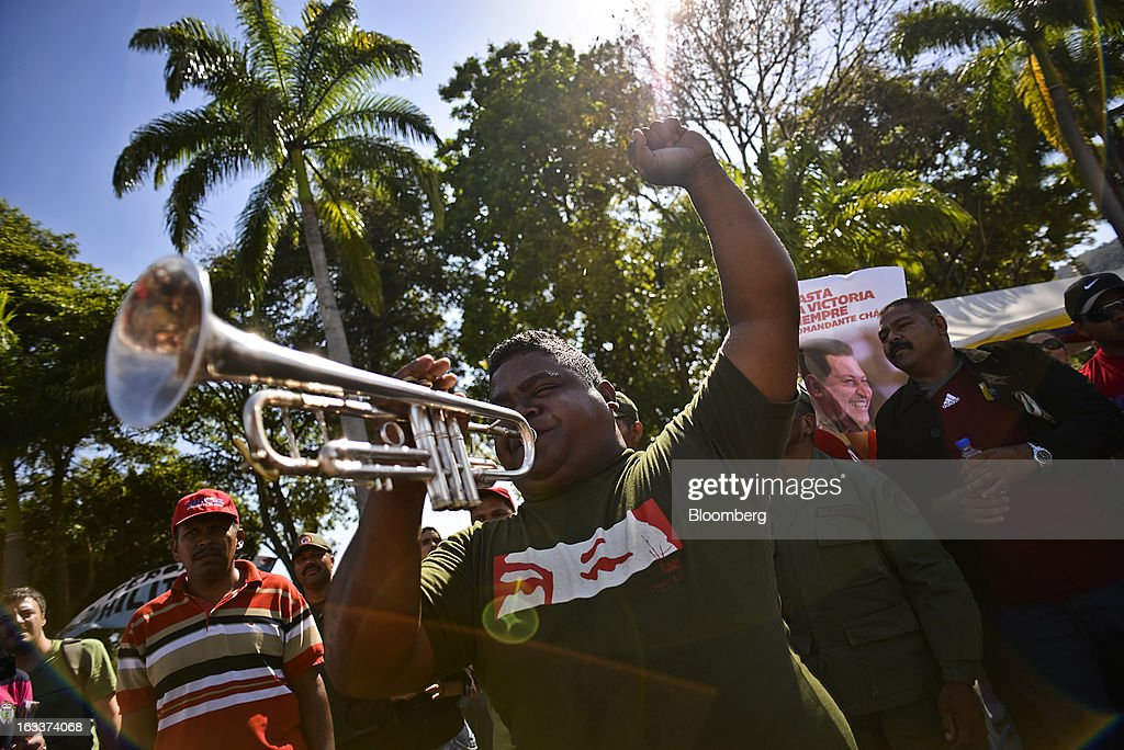 A supporter plays the National Anthem during the funeral for Venezuelan President Hugo Chavez in Caracas, Venezuela, on Friday, March 8, 2013. Allies of Venezuela's Hugo Chavez paid their final respects to the firebrand socialist leader at a state funeral that marked the emotional high point of a week of tributes preceding a snap election to choose his successor. Photographer: Meridith Kohut/Bloomberg via Getty Images