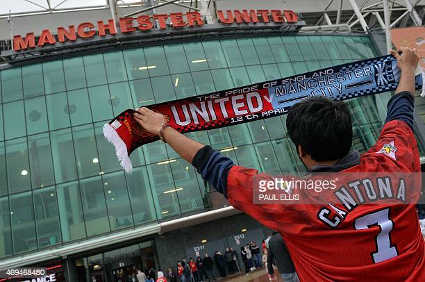 A supporter poses for a photograph holding a 'halfandhalf' Manchester United and Manchester City scarf ahead of the English Premier League football...