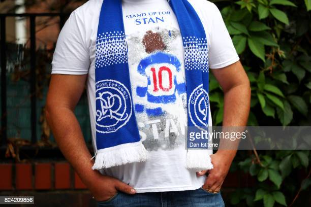 QPR supporter poses outside the stadium wearing a tshirt in tribute to former player Stan Bowles ahead of his benefit match and the preseason...