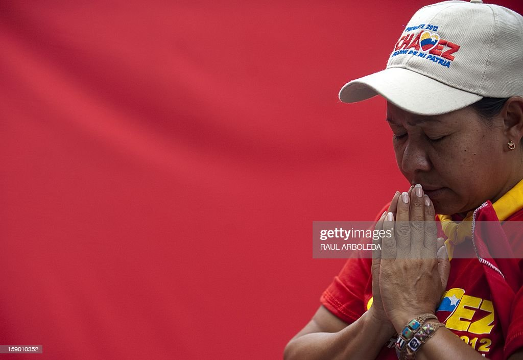 A supporter prays for Venezuelan President Hugo Chavez's health outside the National Assembly in Caracas on January 5, 2013. Venezuelan lawmakers gathered Saturday for a key leadership vote and debate as President Hugo Chavez's battle with cancer appeared almost certain to delay his swearing-in for a new six year term. AFP PHOTO/Raul ARBOLEDA
