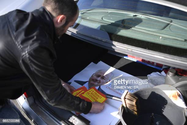 A supporter prepare to paster electoral posters of French presidential election candidate for the Solidarite et Progres party Jacques Cheminade in Le...