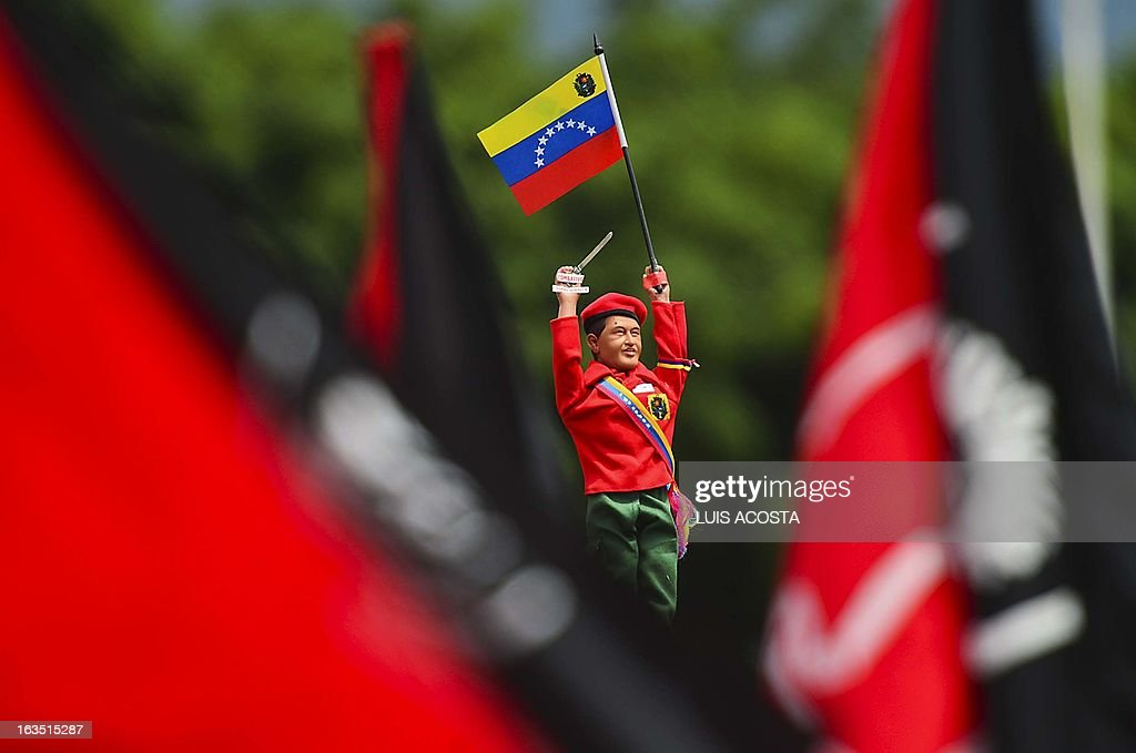 A supporter raises a dummy of late President Hugo Chavez as President in Charge Nicolas Maduro (not depicted) speaks during the official registration of his candidacy for the upcoming presidential election at the National Electoral Council (SNE) in Caracas, on March 11, 2013. Venezuela has entered a bitter election race to succeed Hugo Chavez, with his chosen successor branding his challenger a 'fascist' after the opposition candidate accused him of exploiting the late leader's death. AFP PHOTO/Luis Acosta