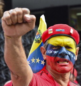 A supporter raises his clenched fist as he listens to the speech of acting president Nicolas Maduro during the official registration of his candidacy...