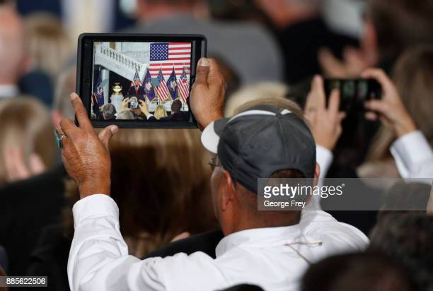 A supporter records on an tablet as US President Donald Trump speaks at the Rotunda of the Utah State Capitol on December 4 2017 in Salt Lake City...