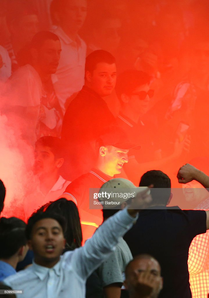 A supporter removes a flare after it was ignited in the Melbourne Victory supporters area of the crowd during the round 19 A-League match between Melbourne City FC and Melbourne Victory at AAMI Park on February 13, 2016 in Melbourne, Australia.
