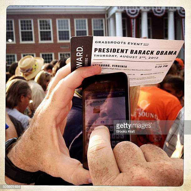 A supporter sends a photo on his mobile phone during a campaign rally for US President Barack Obama at Loudoun County High School in Leesburg Virginia