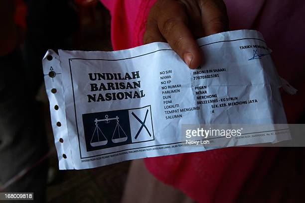 A supporter shows her gift bag coupon while waiting for Malaysia's Prime Minister and Barisan Nasional chairman Najib Razak during an election rally...