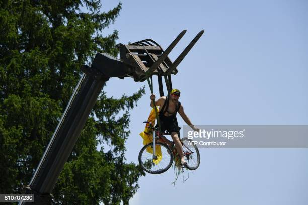 TOPSHOT A supporter sits on a bike suspended from a crane along the road during the 1875 km eighth stage of the 104th edition of the Tour de France...