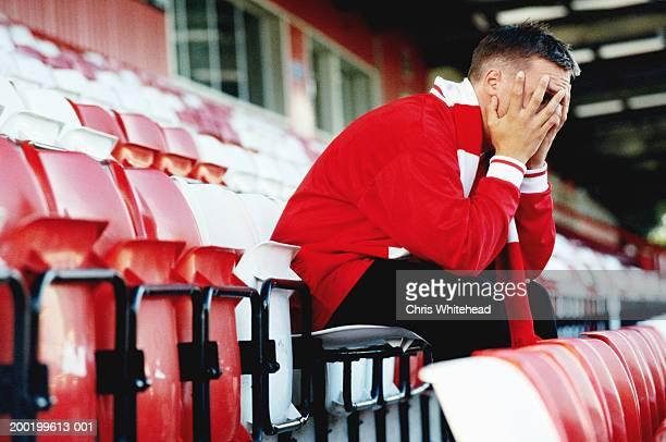 Supporter sitting in empty football stadium, head in hands