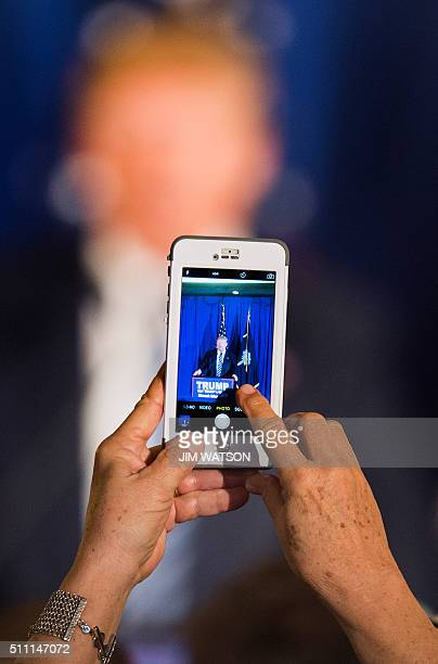 A supporter takes a cell phone photo as Republican presidential candidate Donald Trump speaks during a campaign rally in Kiawah Island South Carolina...