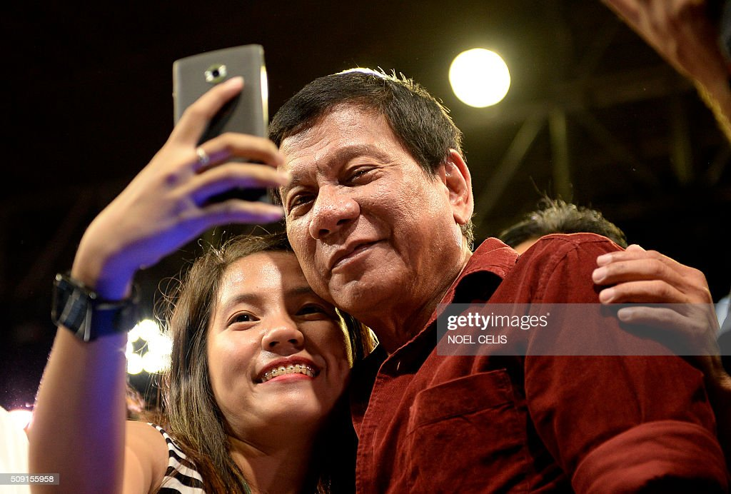 A supporter takes a selfie with Davao City mayor and presidential candidate Rodrigo Duterte during his party's proclamation rally in Manila on February 9, 2016. A cliffhanger race to lead the Philippines began February 9 with the adopted daughter of a dead movie star and a tough-talking politician who claims to kill criminals among the top contenders. AFP PHOTO / NOEL CELIS / AFP / NOEL CELIS