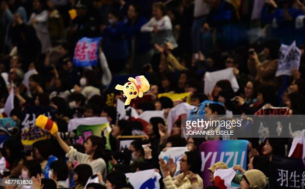 A supporter throws a Pikachu stuffed toy onto the ice after the performance of Yuzuru Hanyu of Japan during the men's short program of the 2015 ISU...