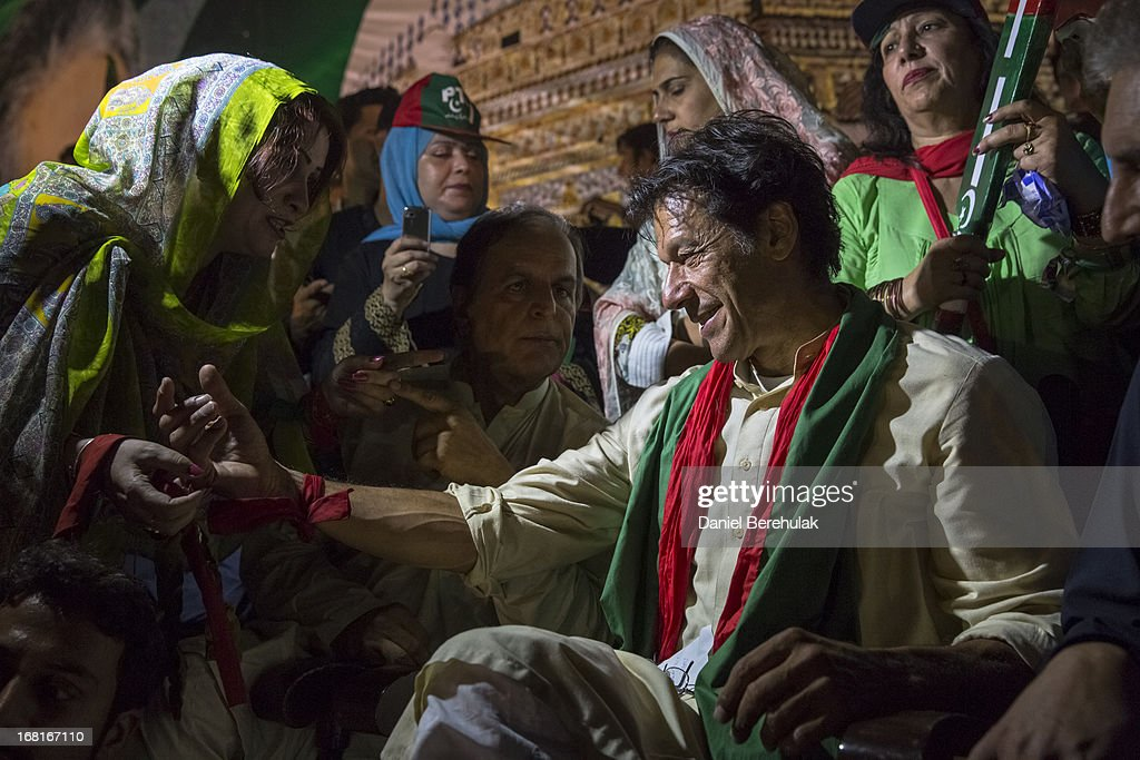 A supporter ties a party ribbon onto the arm of Imran Khan chairman of the Pakistan Tehrik e Insaf party during an election campaign rally on May 06...
