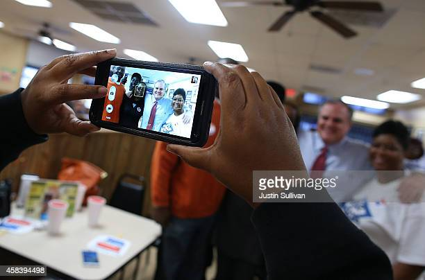 A supporter uses a smartphone to take a photo of US Sen Mark Pryor as greets customers at Sim's BBQ on November 4 2014 in Little Rock Arkansas As...