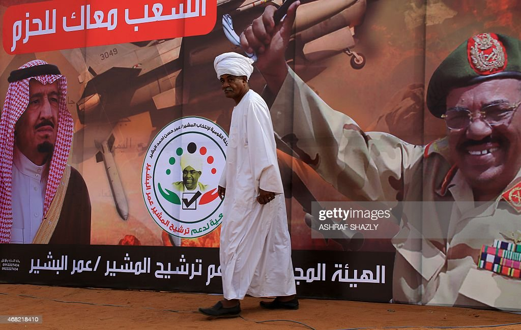 A supporter walks past a banner during a campaign meeting of the incumbent president and candidate of the ruling National Congress Party (NCP) for Sudans presidency Omar al-Bashir on March 31, 2015 in the capital Khartoum, ahead of the April 13 parliamentary and presidential elections. The National Electoral Commission has said some 14 candidates are competing with Bashir for the presidency but most are little-known and pose no real threat to his reelection bid. On the banner are portraits of Bashir and Saudi King Salman bin Abdulaziz al-Saud (L).