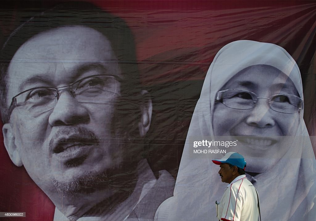 A supporter walks past a banner of Malaysian opposition leader <a gi-track='captionPersonalityLinkClicked' href=/galleries/search?phrase=Anwar+Ibrahim&family=editorial&specificpeople=600601 ng-click='$event.stopPropagation()'>Anwar Ibrahim</a> (L) and his wife Wan Azizah (R) at the Federal Court for Anwar's verdict on sodomy appeal in Putrajaya, outside Kuala Lumpur on February 10, 2015. Malaysian opposition leader <a gi-track='captionPersonalityLinkClicked' href=/galleries/search?phrase=Anwar+Ibrahim&family=editorial&specificpeople=600601 ng-click='$event.stopPropagation()'>Anwar Ibrahim</a> finds out February 10 whether he will be jailed for five years on a controversial sodomy conviction that threatens his political career and the historic rise of the opposition bloc he energised. AFP PHOTO / MOHD RASFAN