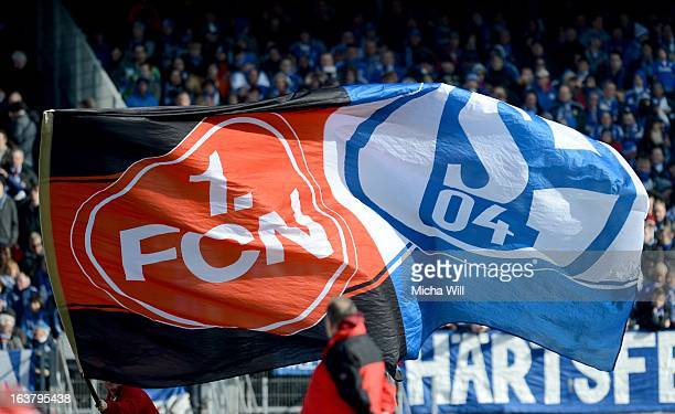 A supporter waves a flag displaying the logos of both clubs prior to the Bundesliga match between 1 FC Nuernberg and FC Schalke 04 at GrundigStadion...