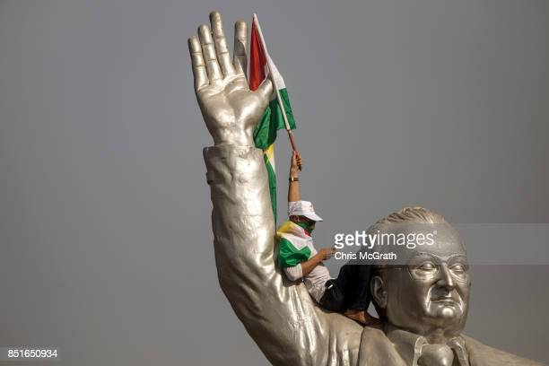 A supporter waves a flag from the stadium statue of Franso Hariri as he waits for the arrival of Kurdish President Masoud Barzani during a rally for...