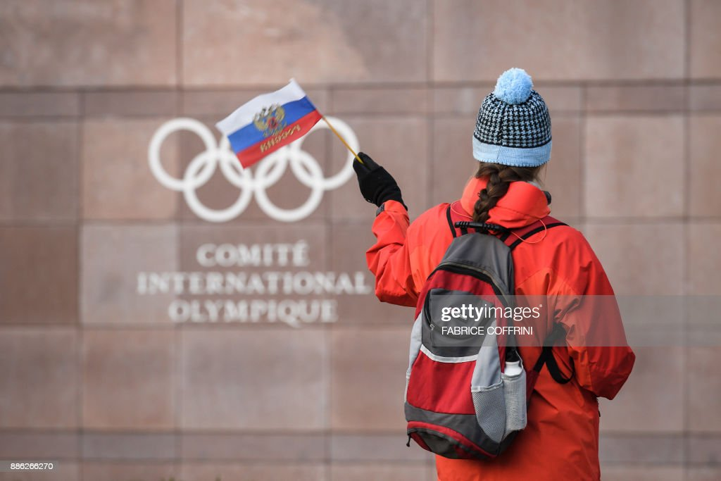 TOPSHOT - A supporter waves a Russian flag in front of the logo of the International Olympic Committee (IOC) at their headquarters on December 5, 2017 in Pully near Lausanne. The International Olympic Committee opened a high-stakes summit on December 5 on whether to bar Russia from the Winter Olympics over allegations its medal haul at the 2014 Sochi Games was fuelled by state-sponsored doping. / AFP PHOTO / Fabrice COFFRINI