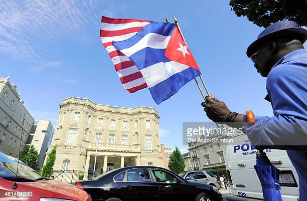 A supporter waves flags of the United States and Cuba in front of the country's embassy after it reopened for the first time in 54 years on July 20...