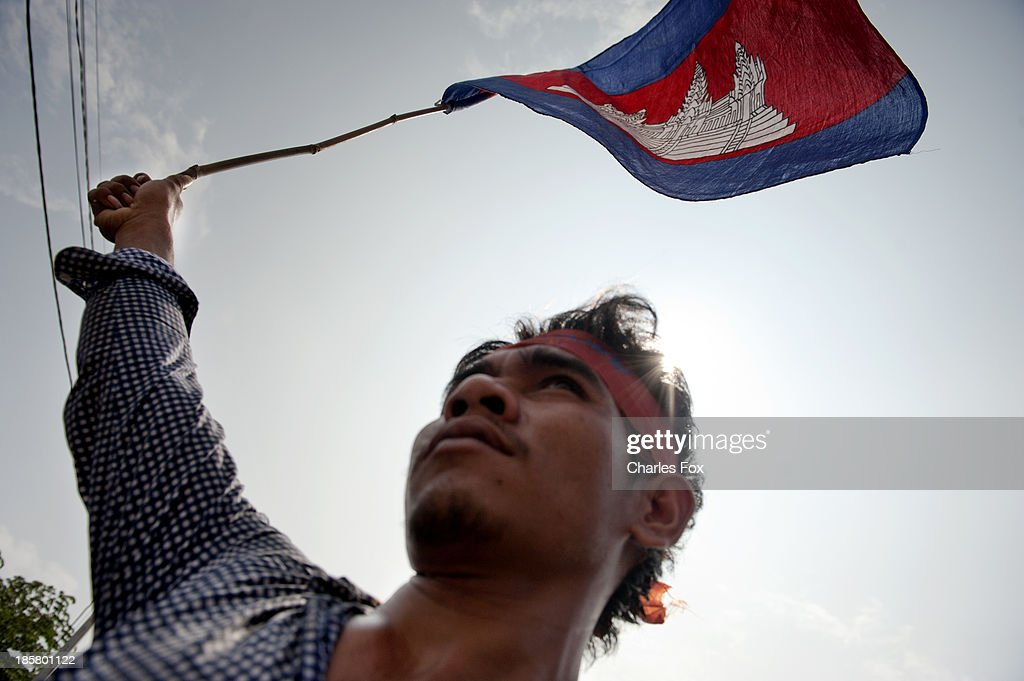 A CNRP supporter waves the Cambodian Nation flag outside of the Austrialian Embassy on October 25, 2013 in Phnom Penh, Cambodia. Today is the last day of a three day protest held by the Cambodian National Rescue Party hold in commemoration of the 22nd anniversary of the October 23, 1991 Paris Peace Accords. The CNRP delivered letters to the Australian, Russian, Japanese, Indonesian and Chinese Embassies asking them to put pressure on the Cambodian government to resolve the current political deadlock caused by a dispute over the country's July elections.