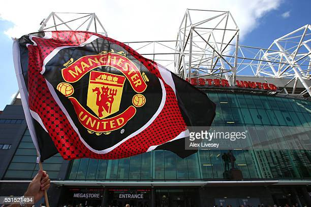A supporter waves the flag prior to the Barclays Premier League match between Manchester United and AFC Bournemouth at Old Trafford on May 15 2016 in...