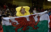 A supporter wearing a daffodil hat holds a Welsh flag before a Pool A match of the 2015 Rugby World Cup between Wales and Fiji at the Millennium...