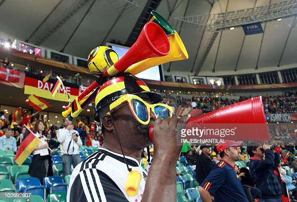 A supporter wearing a makarapa blows a vuvuzela during the 2010 World Cup semifinal football match Germany vs Spain on July 7 2010 at Moses Mabhida...