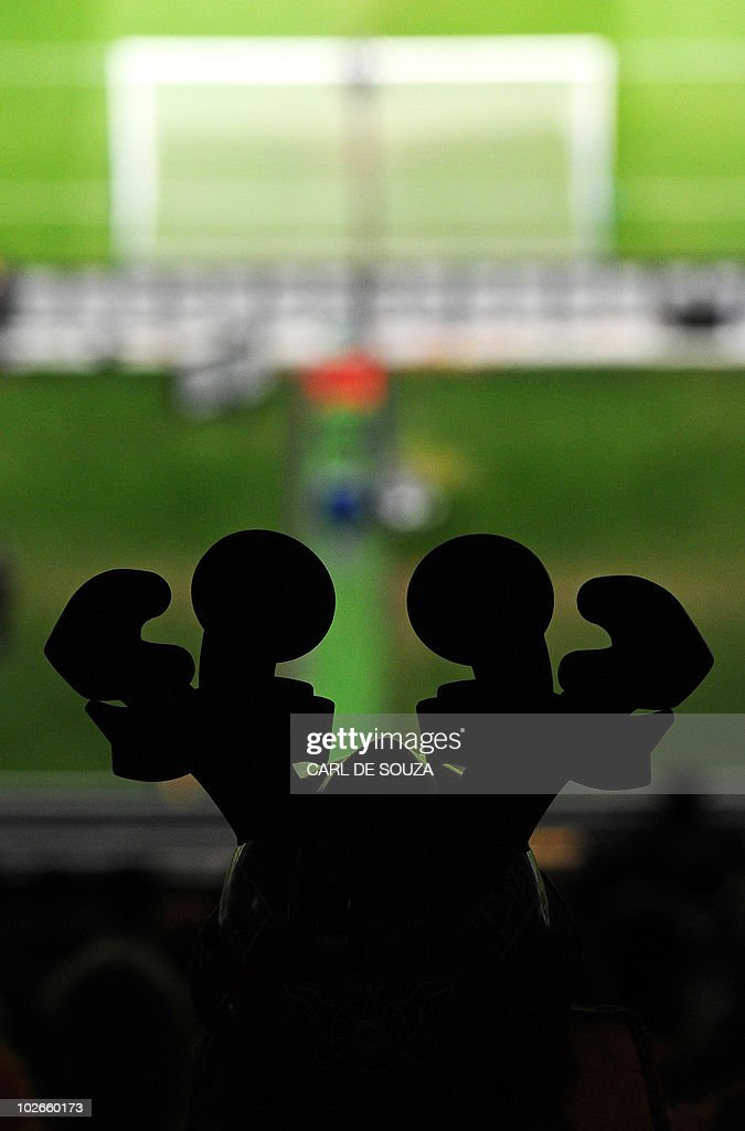 A supporter wearing a makarapa is silhouetted as he watches the 2010 Football World Cup semifinal match Uruguay vs The Netherlands at Green Point...