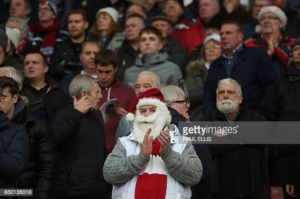 A supporter wears a Father Christmas beard and red Santa hat as he waits in the stands ahead of the English Premier League football match between...
