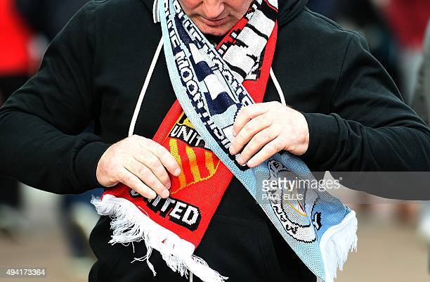 A supporter wears a half and half scarf ahead of the English Premier League football match between Manchester United and Manchester City at Old...