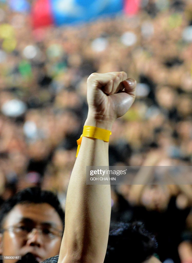 A supporter with a yellow ribbon tied around his wrist, as a symbol of fair and clean election, cheers as opposition leader Anwar Ibrahim (not pictured) speaks during a rally at a stadium in Kelana Jaya, Selangor on May 8, 2013. Vowing to 'never surrender', opposition leader Anwar Ibrahim called on Malaysians to join in a nationwide protest tour against elections he said were stolen through fraud by the coalition that has ruled for 56 years.